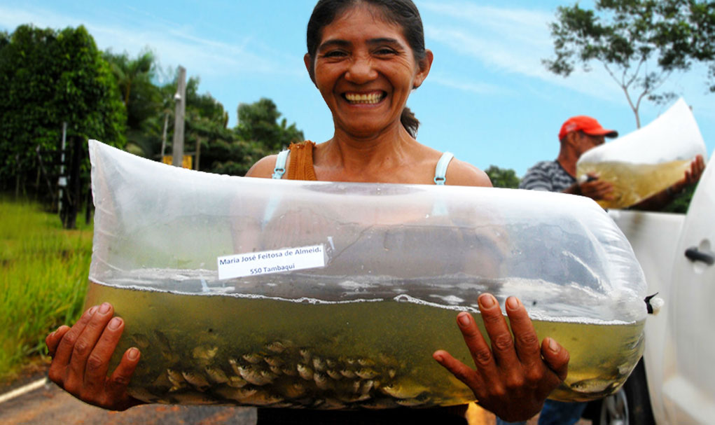 Maria Jose Feitosa a women farmer holding a fishbowl full of live fish made out of a plastic bag